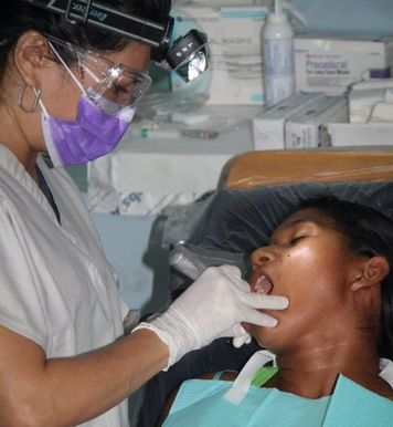 Patient on dental chair being treated by volunteer with Christ Smiles Dental Mission